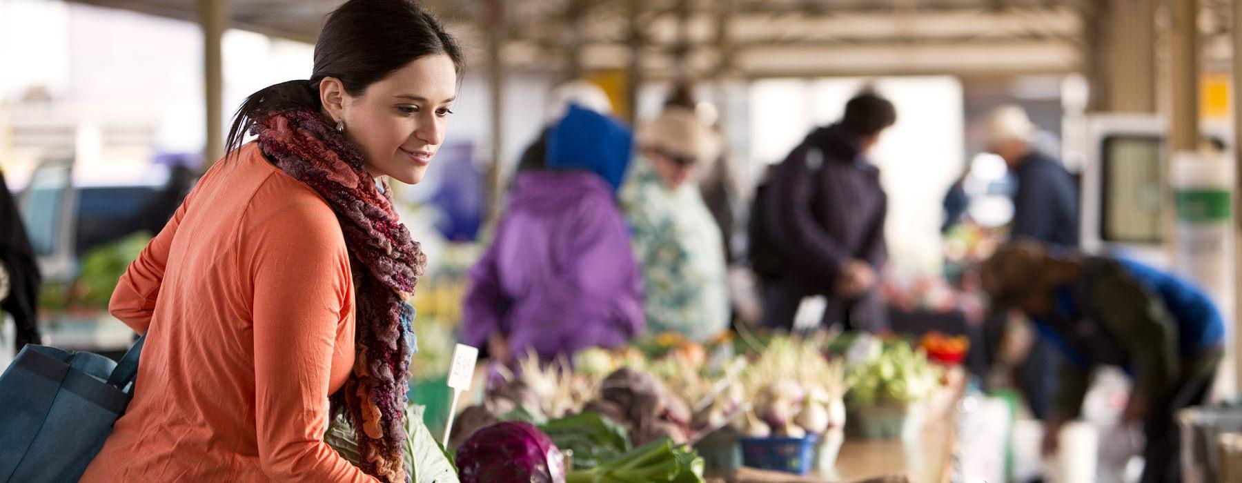 A women smiles while shopping in a vibrant outdoor market.